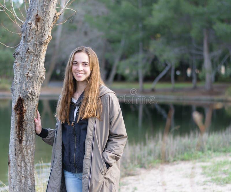 Unga kvinnor poserar utomhus bredvid ett träd och en sjö royaltyfri bild
