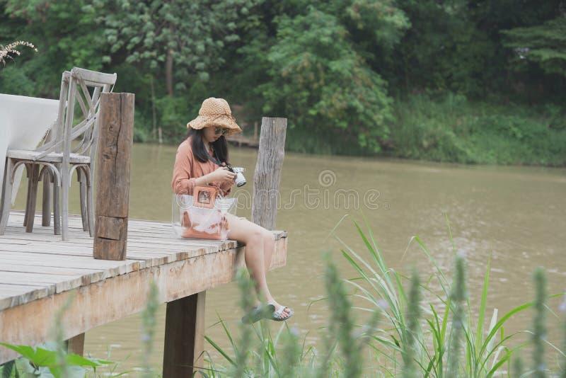 Unga kvinnor rymmer kameran som sitter på träbron royaltyfri fotografi