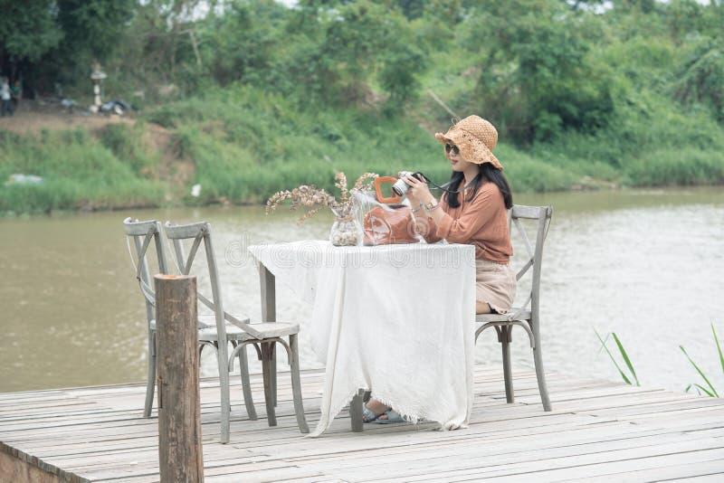 Unga kvinnor rymmer kameran som sitter på träbron och floden på bakgrund royaltyfri foto