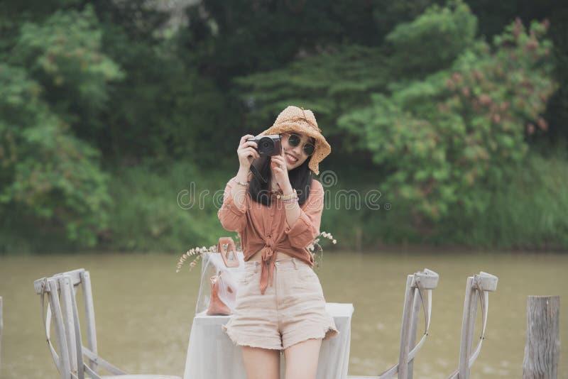 Unga kvinnor rymmer kameran som sitter på träbron och floden på bakgrund arkivbild