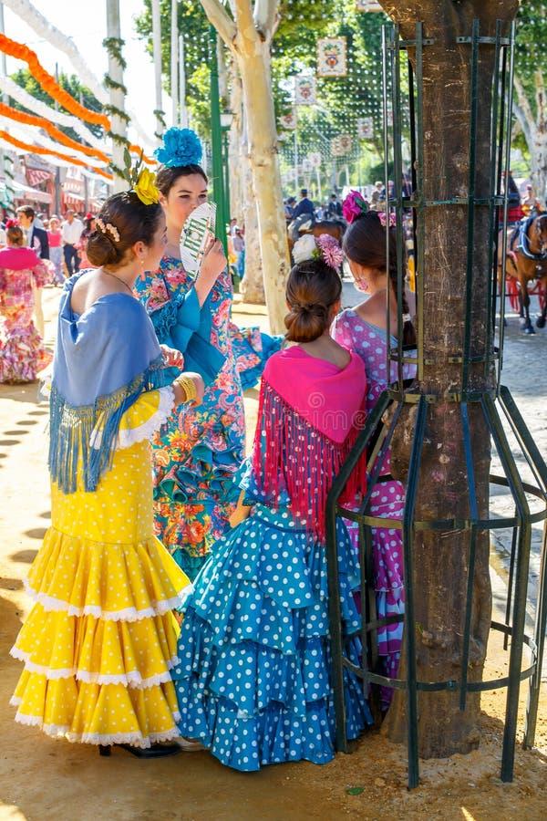 Unga kvinnor som är avslappnande, och iklädda traditionella dräkter på den Seville `en s April Fair royaltyfria foton