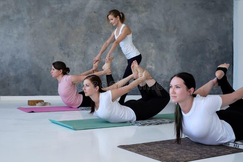 Unga kvinnor som öva yoga som gör den Dhanurasana övningen, pilbågen poserar fotografering för bildbyråer