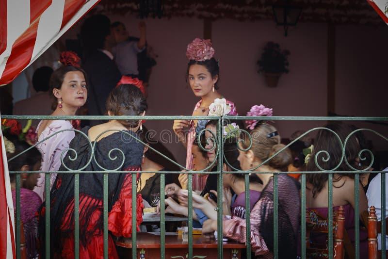 Unga kvinnor som bär traditionell flamenco, klär på April Fair Seville royaltyfria bilder