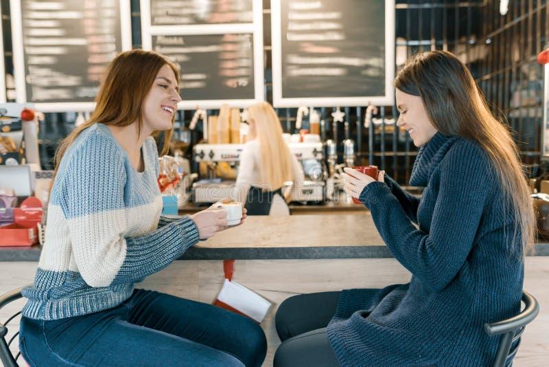 Unga kvinnor som dricker kaffe i kafét, flickor som sitter nära stångräknaren arkivbilder