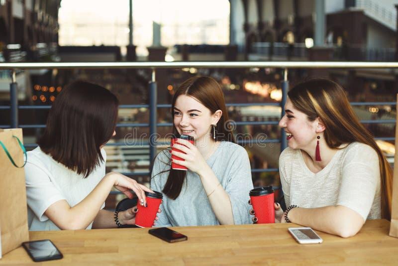 Unga kvinnor som dricker kaffe på kafét i gallerian royaltyfria bilder