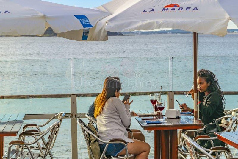 Unga kvinnor som dricker på strandstången royaltyfri fotografi