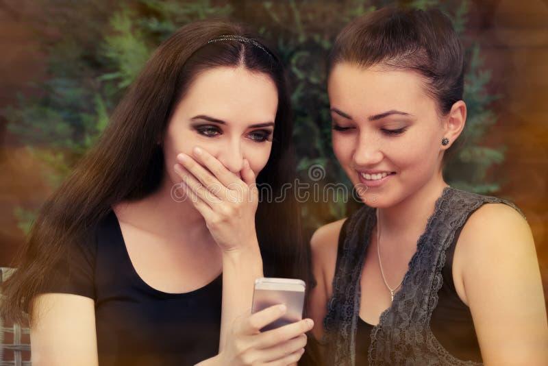 Unga kvinnor som förvånas av textmeddelandet royaltyfri fotografi