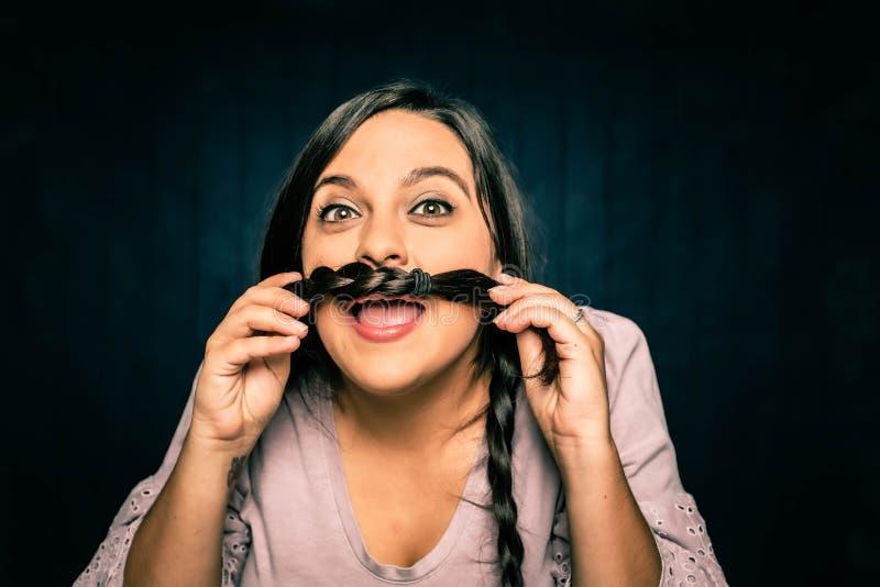 Unga kvinnor som gör en Mustache med sin Braid arkivbild