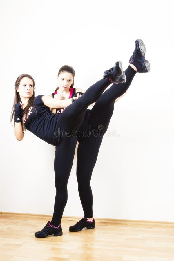 Unga kvinnor som gör sparkboxning arkivbild