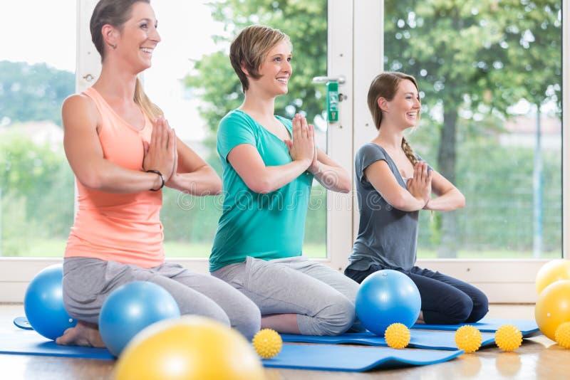 Unga kvinnor som gör yoga under postnatal återställningskurs arkivbild