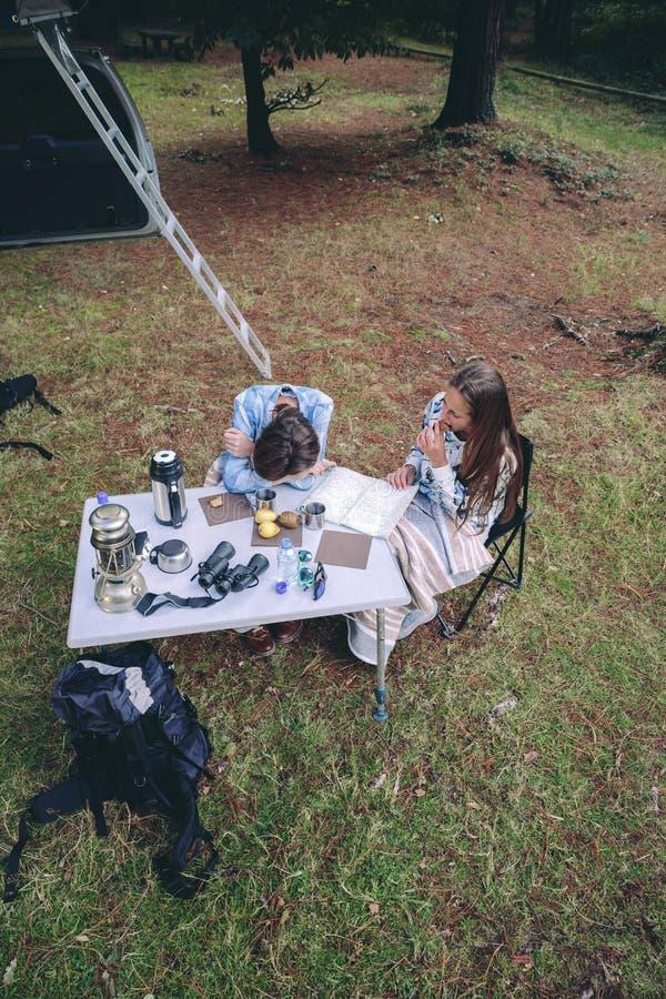Unga kvinnor som har frukosten i en campingplats royaltyfri foto