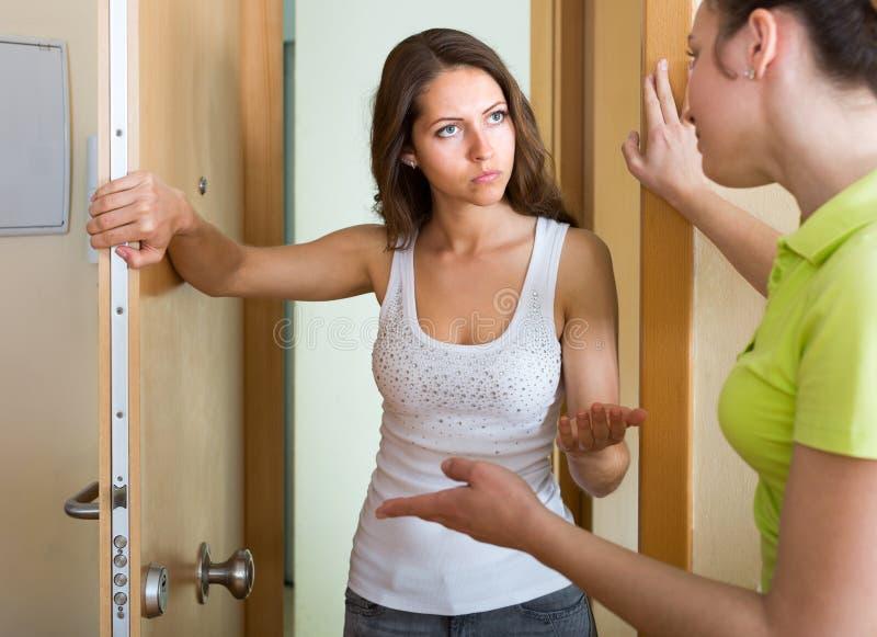 Unga kvinnor som har konflikt på dörren royaltyfria foton