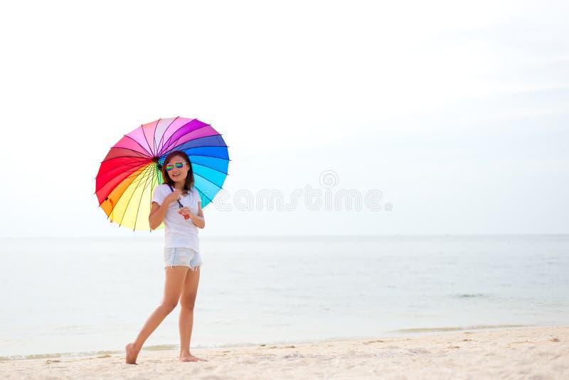 Unga kvinnor som hoppar med paraplyet och som är lyckliga på stranden arkivbilder