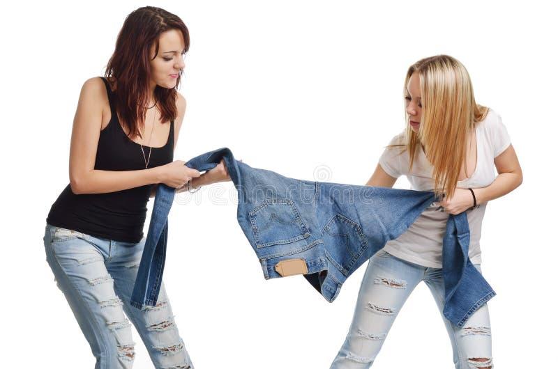Unga kvinnor som kämpar för jeans arkivbild