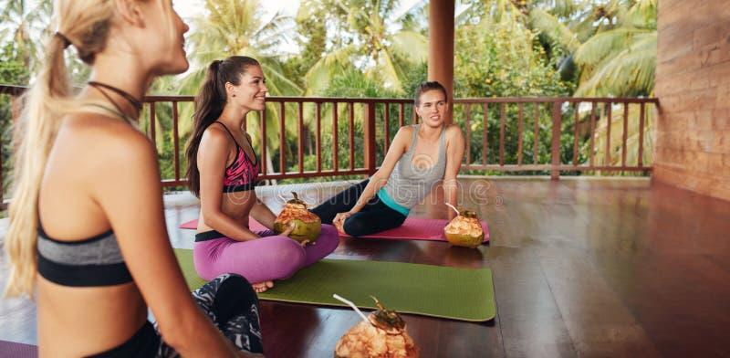 Unga kvinnor som kopplar av med kokosnötfruktsaft på yogagrupp arkivfoton