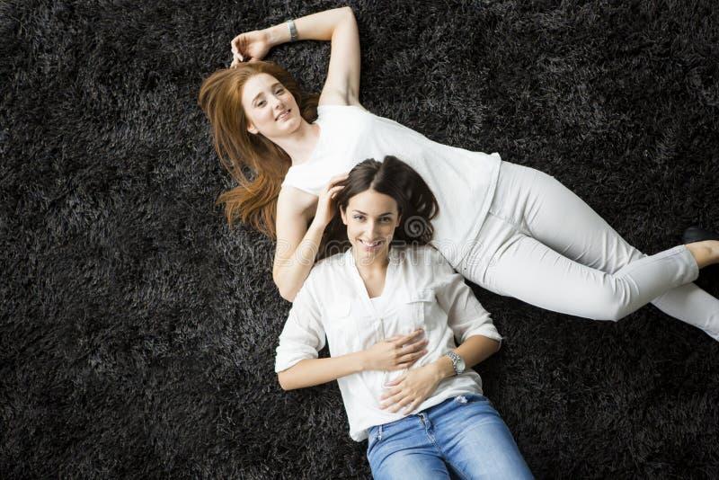 Unga kvinnor som lägger på mattan royaltyfri bild