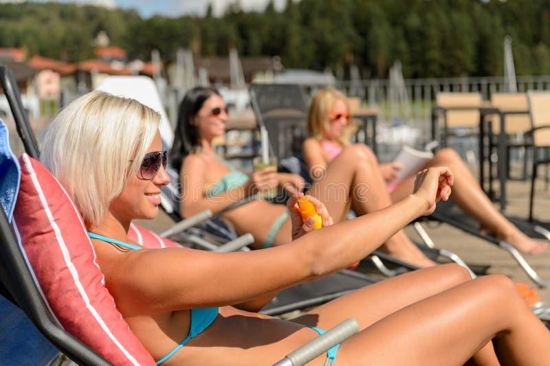 Unga kvinnor som ligger på deckchair som applicerar sunscreen arkivfoton