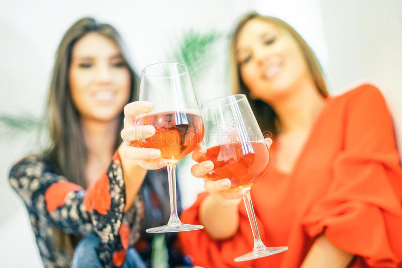 Unga kvinnor som rostar exponeringsglas av rosa vin i deras hem - lyckliga systrar som tycker om deras tid som dricker tillsamman arkivbild