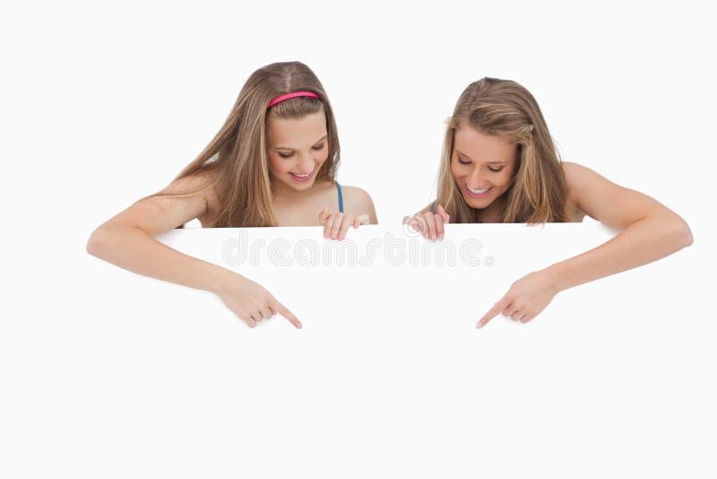 Unga kvinnor som rymmer och pekar ett blankt tecken arkivbild