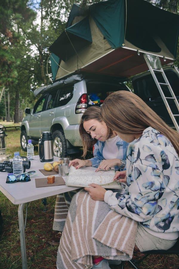 Unga kvinnor som ser färdplanen med medlet på bakgrund fotografering för bildbyråer