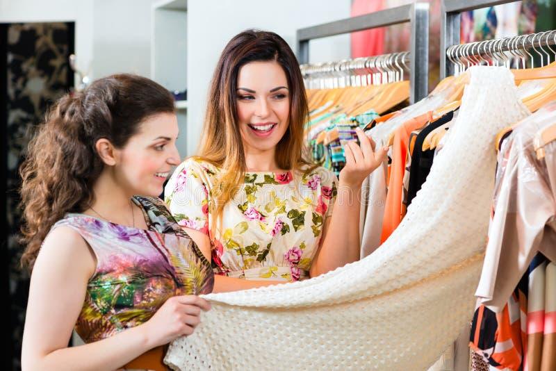 Unga kvinnor som shoppar mode i varuhus arkivbilder