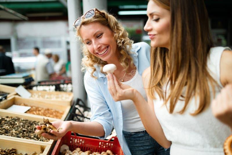 Unga kvinnor som shoppar på de sunda grönsakerna och frukterna för marknad arkivbild