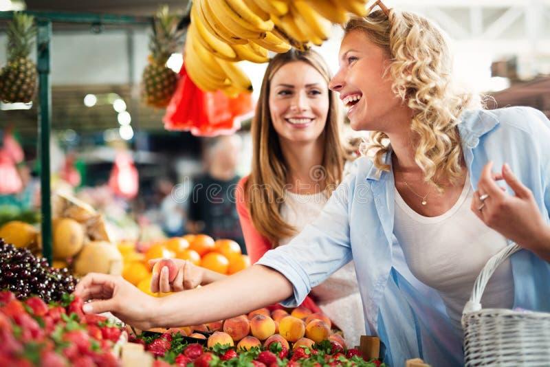 Unga kvinnor som shoppar på de sunda grönsakerna och frukterna för marknad royaltyfri fotografi