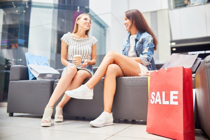 Unga kvinnor som shoppar på Sale arkivfoton