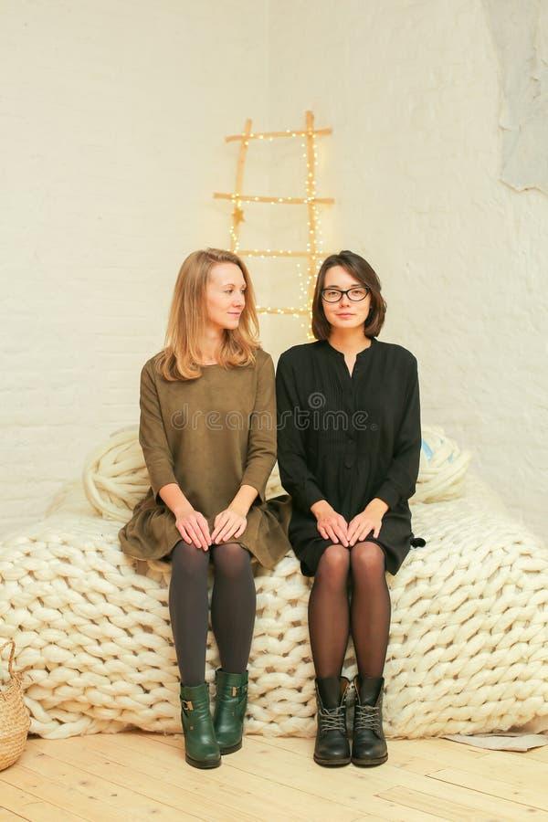 Unga kvinnor som sitter i den vita inre arkivbild