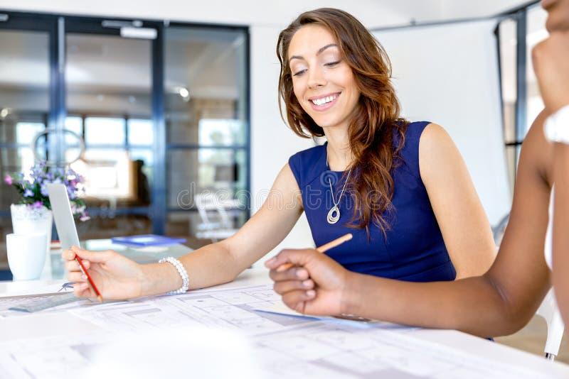 Unga kvinnor som sitter på ett skrivbord i ett kontor och ett arbete på ritning royaltyfri bild