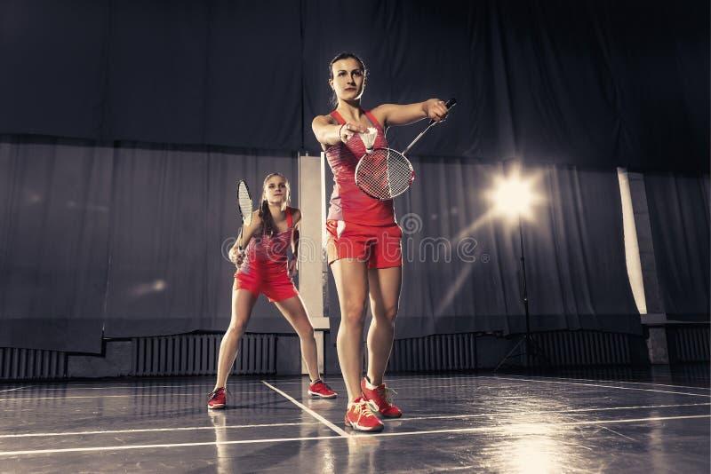 Unga kvinnor som spelar badminton på idrottshallen arkivfoto