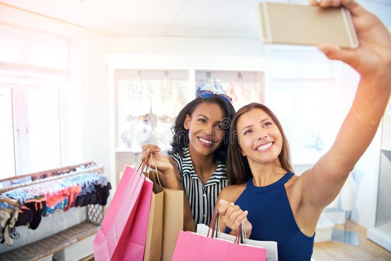 Unga kvinnor som tar en selfie i en modeboutique fotografering för bildbyråer