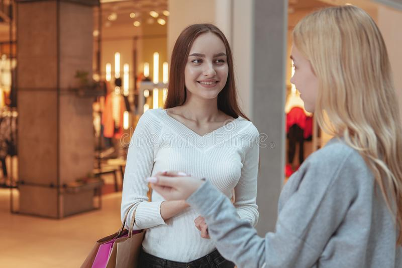 Unga kvinnor som tycker om att shoppa tillsammans på gallerian royaltyfri fotografi