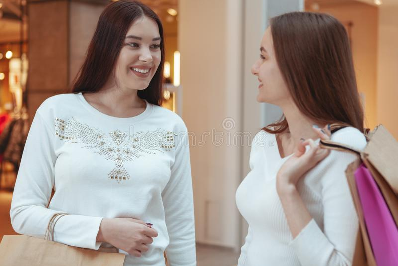Unga kvinnor som tycker om att shoppa tillsammans på gallerian arkivbild