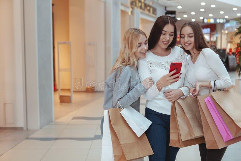 Unga kvinnor som tycker om att shoppa tillsammans på gallerian royaltyfri foto