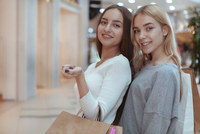 Unga kvinnor som tycker om att shoppa tillsammans på gallerian royaltyfri bild