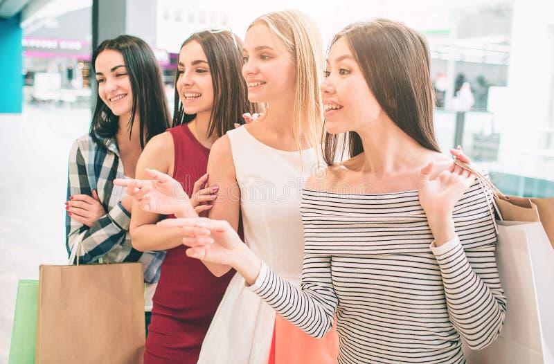 Unga kvinnor står en, når andra och de har poserat Den asiatiska flickan står framme De ser till det vänstert och arkivbilder
