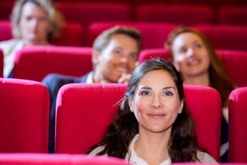 Unga kvinnor tittar på film ensam royaltyfri fotografi