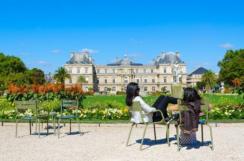 Unga kvinnor vilar i den Luxembourg trädgården nära den Luxembourg slotten, Paris, Frankrike arkivfoton