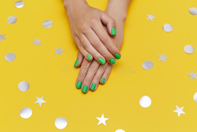 Unga kvinnors händer med ljusgrön manicure på den gula bakgrunden med glänsande silverkonfetti royaltyfri foto