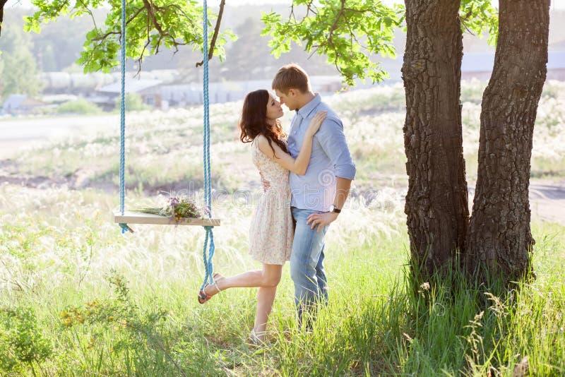 Unga kyssande par under stort träd med gunga royaltyfria foton