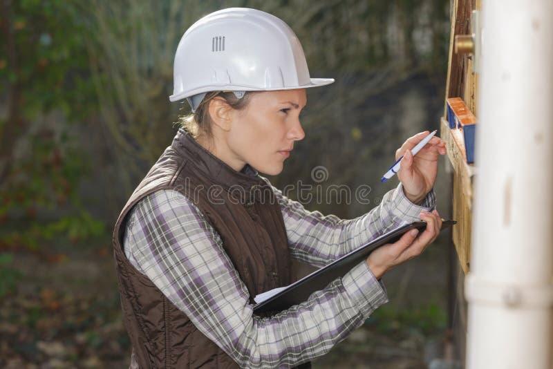 Unga läsningmeter för kvinnlig arbetare royaltyfria foton