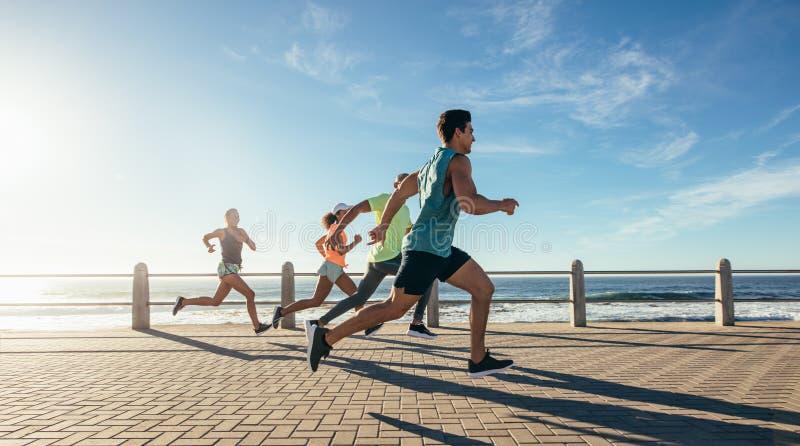 Unga löpare som sprintar på banan för havframdel royaltyfria bilder