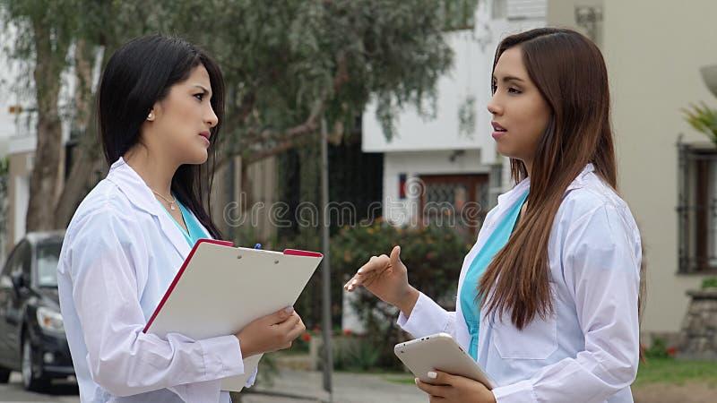 Unga latinamerikanska kvinnligdoktorer eller sjuksköterskor arkivbild