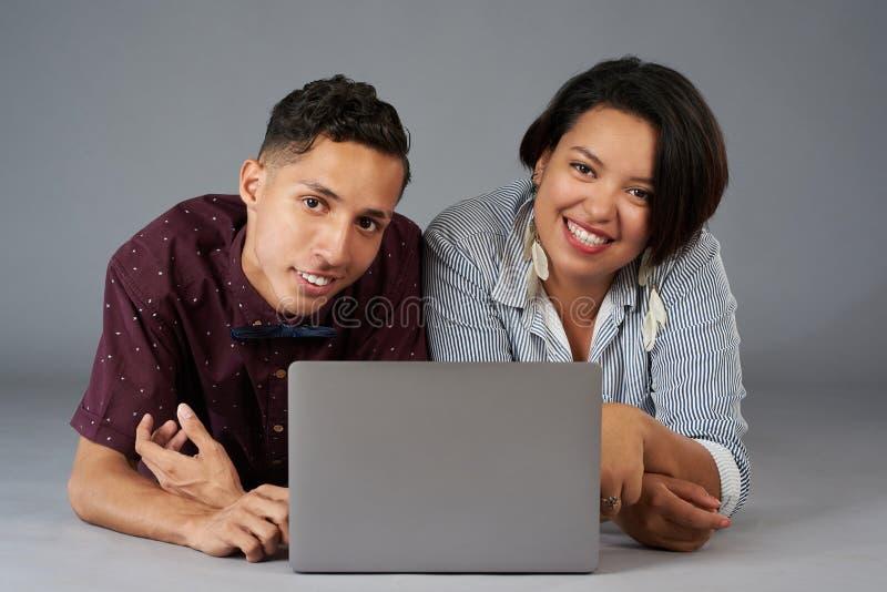 Unga latinamerikanska par genom att använda bärbara datorn royaltyfri bild