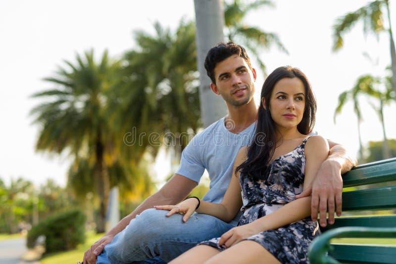 Unga latinamerikanska par som tillsammans kopplar av i parkera royaltyfri foto