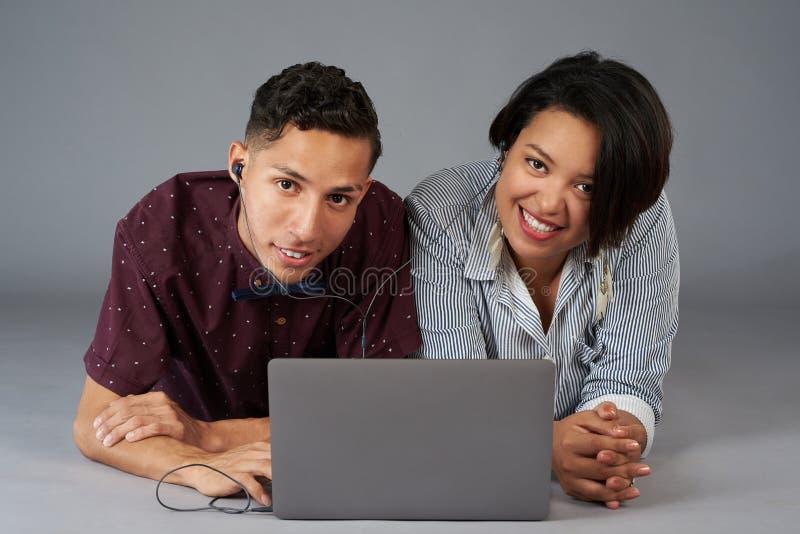 Unga latinska par med earphoners och bärbara datorn royaltyfri bild
