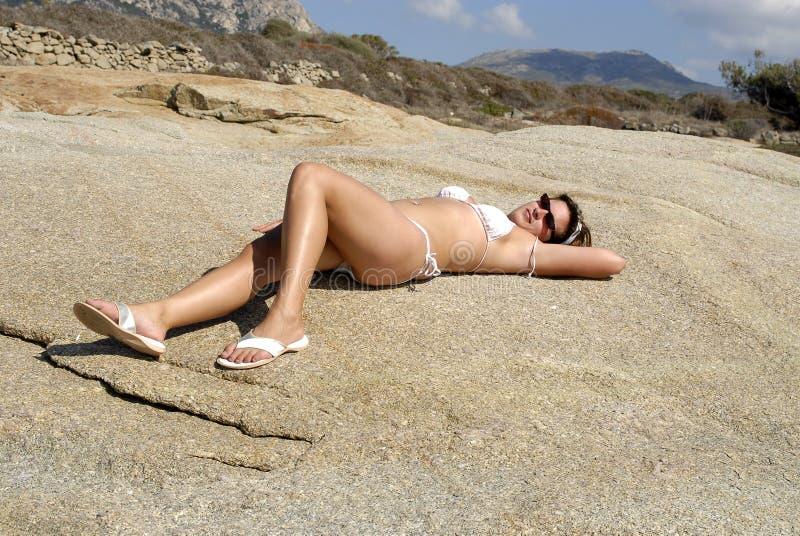 unga liggande rocks för bikiniflicka royaltyfri fotografi
