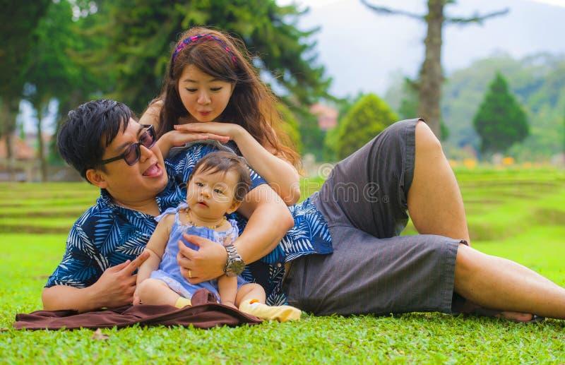 Unga lyckliga älska asiatiska koreanska föräldrar som par som tillsammans tycker om den söta dottern, behandla som ett barn flick royaltyfria bilder