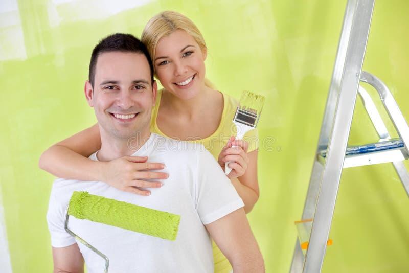 Unga lyckliga behändiga par som målar det nya huset arkivbilder